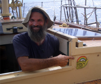 Keith Davies, Skipper of One Off, pointing to the sticker from Rainbow Power who donated a solar power inverter to the project.